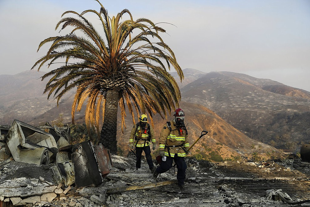 Firefighters Jason Toole, right, and Brent McGill with the Santa Barbara Fire Dept. walk among the ashes of a wildfire-ravaged home after turning off an open gas line on the property Saturday, Nov. 10, 2018, in Malibu, Calif. (AP Photo/Marcio Jose Sanchez)