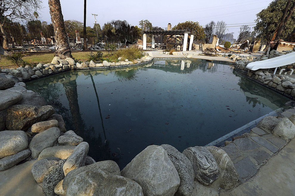A swimming pool is behind one burned home, with others at left, some of at least 20 homes destroyed just on Windermere Drive in the Point Dume area of Malibu, Calif., Saturday, Nov. 10, 2018. Known as the Woolsey Fire, it has consumed tens of thousands of acres and destroyed dozens of homes. (AP Photo/Reed Saxon)