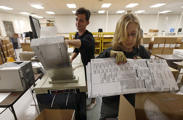Workers organize ballots at the Maricopa County Recorder's Office Thursday, Nov. 8, 2018, in Phoenix. There are several races too close to call in Arizona, especially the Senate race between Democratic candidate Kyrsten Sinema and Republican candidate Martha McSally. (Ross D. Franklin/AP, file)
