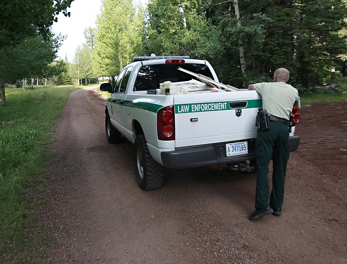 In this Aug. 20, 2010, file photo, a forest service worker breaks down a road block near an eastern Arizona campground on the Apache-Sitgreaves National Forest. (Matt York/AP, file)