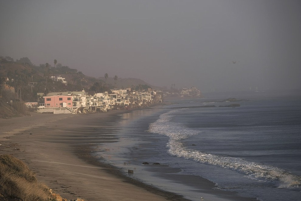 Thick smoke envelops the Malibu Colony along the pacific coast in Malibu, Calif. on Sunday Nov. 11, 2018. Strong Santa Ana winds have returned to Southern California, fanning a huge wildfire that has scorched a string of communities west of Los Angeles. A one-day lull in the dry, northeasterly winds ended Sunday morning and authorities warn that the gusts will continue through Tuesday. (AP Photo/Richard Vogel)