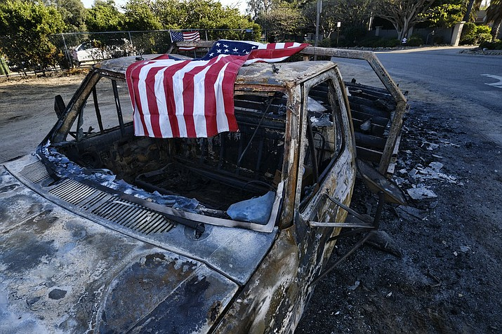 An American flag is draped over the charred remains of an old pickup truck entering Point Dume along the pacific coast highway in Malibu, Calif., on Sunday Nov. 11, 2018. Strong Santa Ana winds have returned to Southern California, fanning a huge wildfire that has scorched a string of communities west of Los Angeles. A one-day lull in the dry, northeasterly winds ended Sunday morning and authorities warn that the gusts will continue through Tuesday. (AP Photo/Richard Vogel)