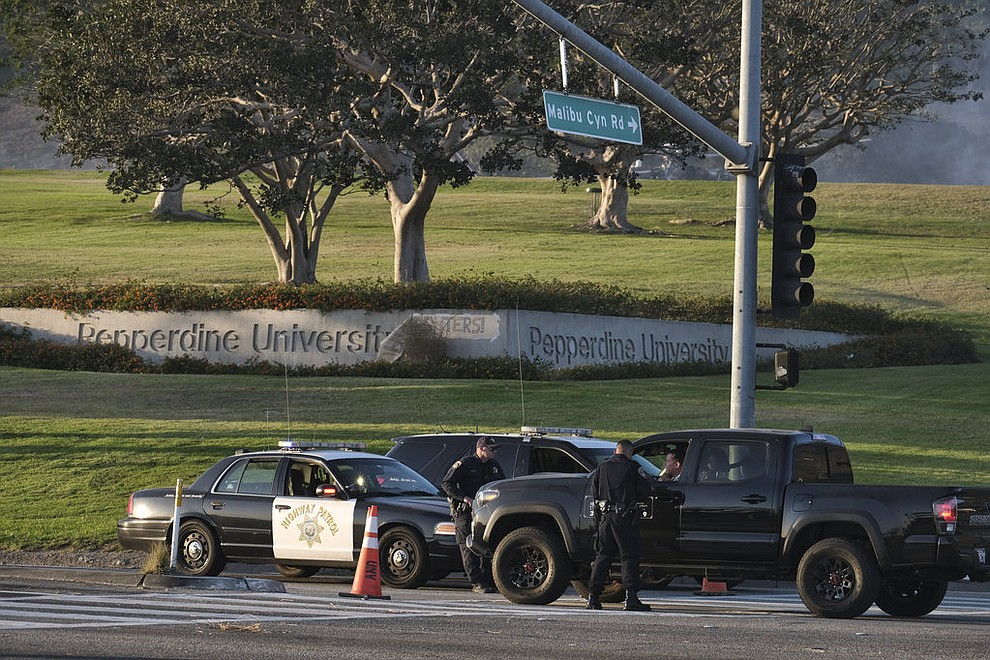 California Highway Patrol block off the Pacific Coast Highway in front of Pepperdine University in Malibu, Calif., on Sunday Nov. 11, 2018. Strong Santa Ana winds have returned to Southern California, fanning a huge wildfire that has scorched a string of communities west of Los Angeles. A one-day lull in the dry, northeasterly winds ended Sunday morning and authorities warn that the gusts will continue through Tuesday. (AP Photo/Richard Vogel)