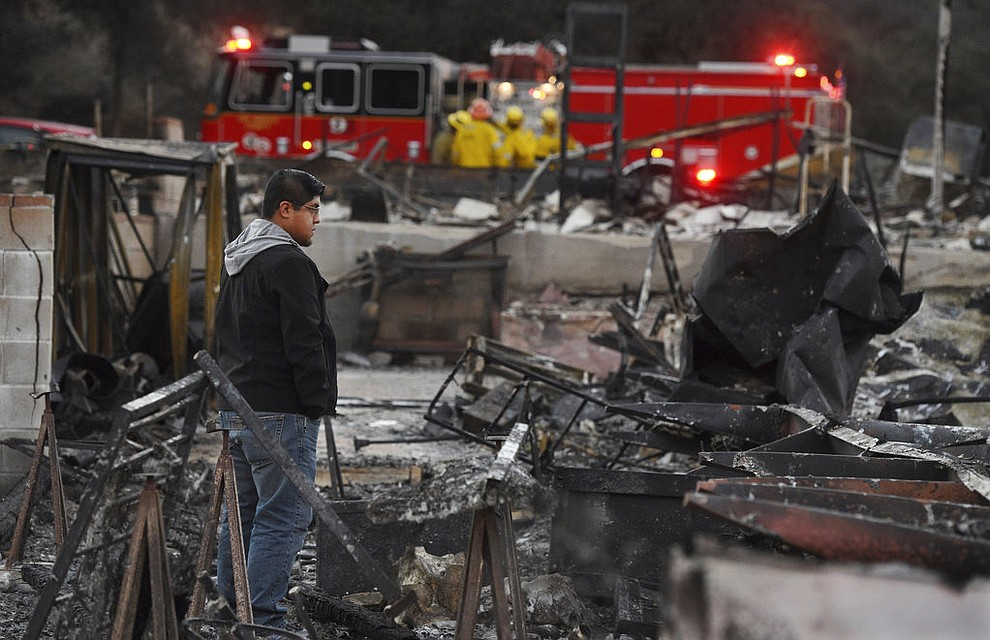Ricky Alvarado looks over the charred remains of his home at the Seminole Springs Mobile Home Park, Sunday, Nov. 11, 2018, after the neighborhood was devastated by wildfires in Agoura Hills, Calif. (AP Photo/Chris Pizzello)