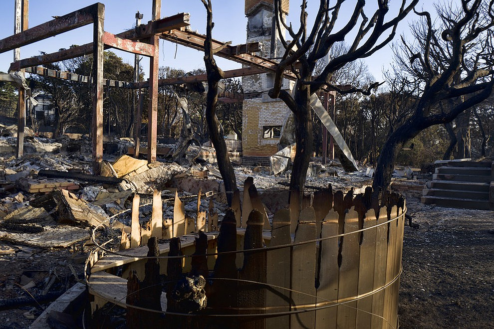 A burned out hot tub and a fireplace are all that remains of a house in Point Dume, Malibu, Calif., Sunday, Nov. 11, 2018. Strong Santa Ana winds have returned to Southern California, fanning a huge wildfire that has scorched a string of communities west of Los Angeles. A one-day lull in the dry, northeasterly winds ended Sunday morning and authorities warn that the gusts will continue through Tuesday. (AP Photo/Richard Vogel)