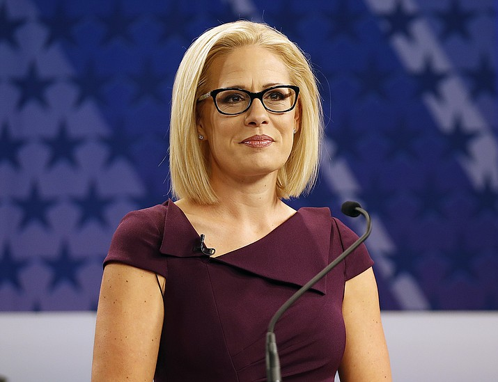 In this Oct. 15, 2018 file photo, U.S. Rep. Kyrsten Sinema appears on a televised debate with U.S. Rep. Martha McSally, R-Ariz., in Phoenix.  (Matt York/AP, file)
