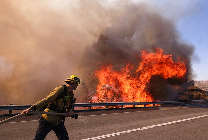 A firefighter battles a fire along the Ronald Reagan (118) Freeway in Simi Valley, Calif., Monday, Nov. 12, 2018. (AP Photo/Ringo H.W. Chiu)