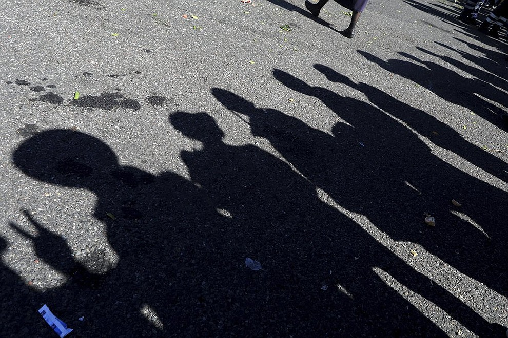 """The shadows of Central American migrants, part of the caravan hoping to reach the U.S. border, stand in a line to board buses, on their way to Mazatlan, Mexico, Tuesday, Nov. 13, 2018. The U.S. government said it was starting work Tuesday to """"harden"""" the border crossing from Tijuana, Mexico, to prepare for the arrival of a migrant caravan leapfrogging its way across western Mexico. (AP Photo/Rodrigo Abd)"""