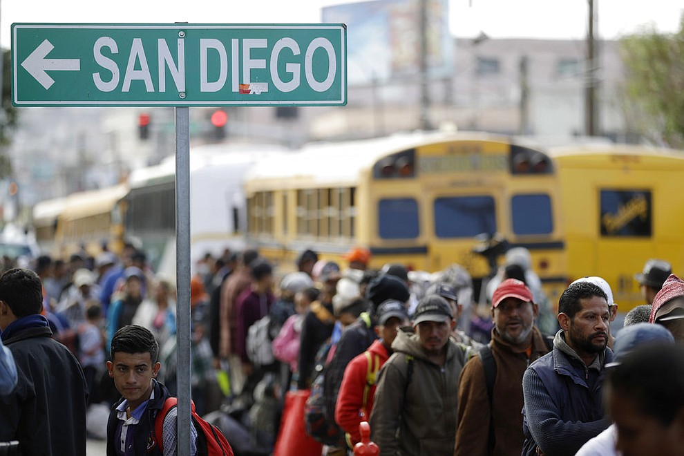 Central American migrants line up for a meal at a shelter in Tijuana, Mexico, Wednesday, Nov. 14, 2018. Migrants in a caravan of Central Americans scrambled to reach the U.S. border, catching rides on buses and trucks for hundreds of miles in the last leg of their journey Wednesday as the first sizable groups began arriving in the border city of Tijuana. (AP Photo/Gregory Bull)