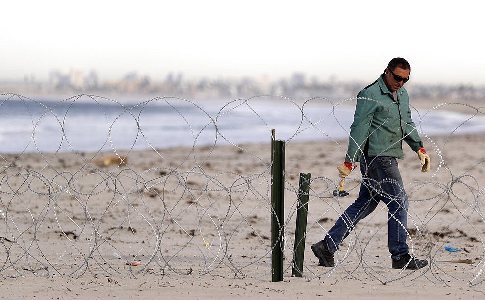 A worker installs concertina wire along the beach closest to the border, as the city of San Diego sits in the distance, as seen from Tijuana, Mexico, Wednesday, Nov. 14, 2018. Migrants in a caravan of Central Americans scrambled to reach the U.S. border, catching rides on buses and trucks for hundreds of miles in the last leg of their journey Wednesday as the first sizable groups began arriving in the border city of Tijuana. (AP Photo/Gregory Bull)