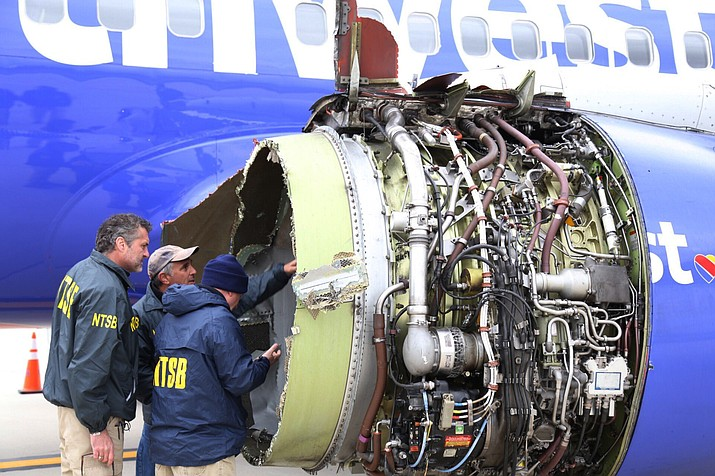 National Transportation Safety Board investigators examine damage to the engine of the Southwest Airlines plane April 17, 2018, that made an emergency landing at Philadelphia International Airport in Philadelphia. (NTSB via AP)