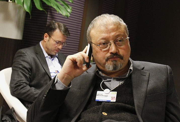 In this Jan. 29, 2011 file photo, Saudi journalist Jamal Khashoggi speaks on his cellphone at the World Economic Forum in Davos, Switzerland. Saud Al-Mojeb, Saudi Arabia's top prosecutor, is recommending the death penalty for five suspects charged with ordering and carrying out the killing of Saudi writer Jamal Khashoggi. Al-Mojeb told a press conference in Riyadh Thursday, Nov. 15, 2018, that Khashoggi's killers had been planning the operation since September 29, three days before he was killed inside the kingdom's consulate in Istanbul. (AP Photo/Virginia Mayo, File)