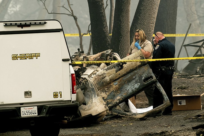 A sheriff's deputy recovers the remains of a Camp Fire victim from an overturned car in Paradise, Calif., on Thursday, Nov. 15, 2018. (Noah Berger/AP)