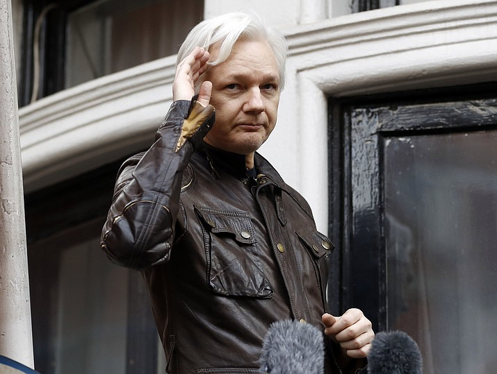 In this May 19, 2017, file photo, WikiLeaks founder Julian Assange greets supporters from a balcony of the Ecuadorian embassy in London. The Justice Department inadvertently named Assange in a court filing in an unrelated case that raised immediate questions about whether the WikiLeaks founder had been charged under seal. Assange's name appears twice in an August 2018 filing from a prosecutor in Virginia in a separate case involving a man accused of coercing a minor. (AP Photo/Frank Augstein, File)