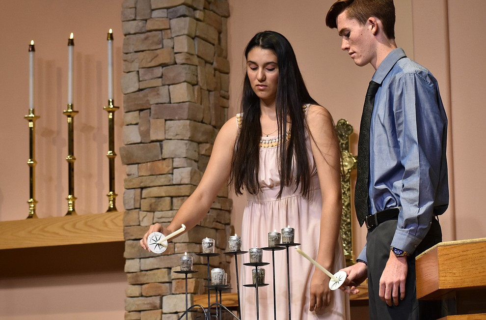 "Jasai Orduno and Dillon Harwood of Unity Church light candles representing different faiths during the opening ceremony of the interfaith Celebration of Thanks event on Nov. 15, 2018 at St. Luke's Episcopal Church in Prescott. The annual event, called ""Many Voices of Thanks,"" brings together choirs, musicians, dancers and speakers from many faith beliefs and is sponsored by the Quad City Interfaith Council. (Richard Haddad/WNI)"