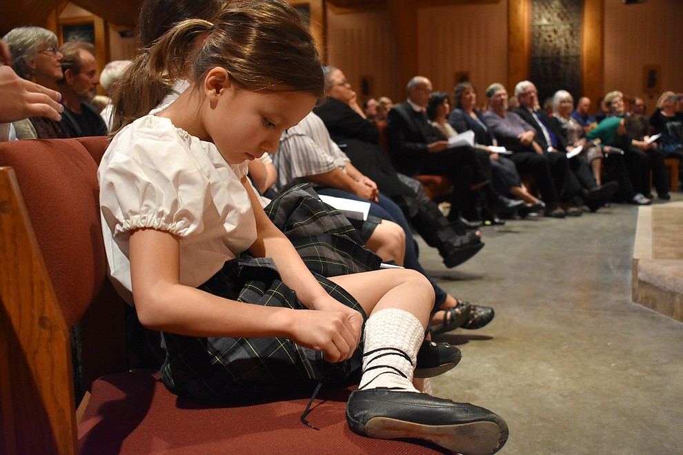 "A young member of the Sacred Heart Children's Irish Dancers tightens her laces during the 2018 Celebration of Thanks concert held Thursday, Nov. 15 at St. Luke's Episcopal Church in Prescott. The annual event, called ""Many Voices of Thanks,"" brings together choirs, musicians, dancers and speakers from many faith beliefs and is sponsored by the Quad City Interfaith Council. (Richard Haddad/WNI)"