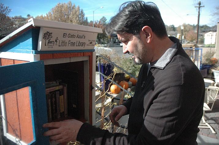 Barry Barbe, owner of El Gato Azul, peers into the Little Free Library right outside the restaurant. (Jason Wheeler/Courier)