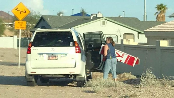 A woman who State Rep. Paul Mosley identified as Lake Havasu City business owner Debi Ashton is shown removing one of Mosley's signs this past summer. (Courtesy)