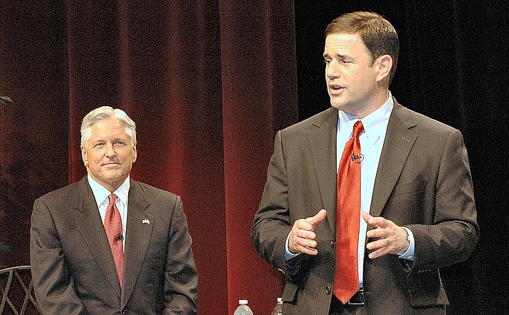 Fred DuVal, seated, listens as Doug Ducey makes a point during their 2014 gubernatorial debate, a debate in which Ducey criticized DuVal for increases in university tuition while he served as president of the Arizona Board of Regents. (Capitol Media Services photo by Howard Fischer)