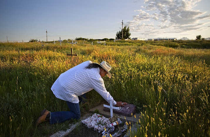 Kenny Still Smoking touches the tombstone of his 7-year-old daughter, Monica, who disappeared from school in 1979 and was found frozen on a mountain, as he visits her grave July 14, 2018, on the Blackfeet Indian Reservation in Browning, Mont. (David Goldman/AP, File)