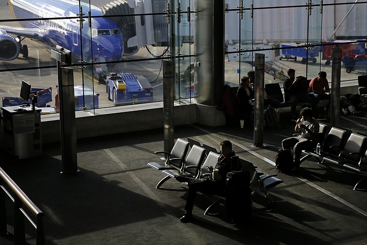 Travelers sit at a gate at Baltimore-Washington International Thurgood Marshall Airport, Tuesday, Nov. 20, 2018, in Linthicum, Md. Favorable weather is helping get the Thanksgiving travel rush off to a smooth start. By midday Tuesday, just a few dozen flights had been canceled around the U.S. That's fewer cancelations than many regular travel days. (AP Photo/Patrick Semansky)