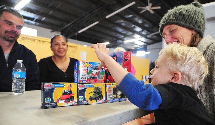 Four-year old Gabe Repak, with mom Colleen McHorney at right, gets some new Lego's from shelter transition residents Jason Brock and Stephanie Andrade to replace the precious one he lost Tuesday, Nov. 13, 2018 at the Center for Compassion and Justice shelter in Prescott.  (Les Stukenberg/Courier)
