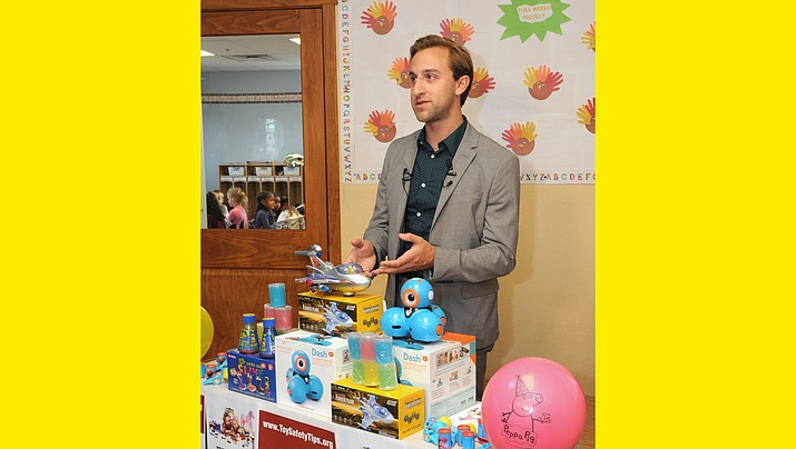 Aaron Kane of the Public Interest Research Group demonstrates toys his organization says parents should avoid – or at least understand the hazards – before buying them for their children. (Capitol Media Services photo by Howard Fischer)