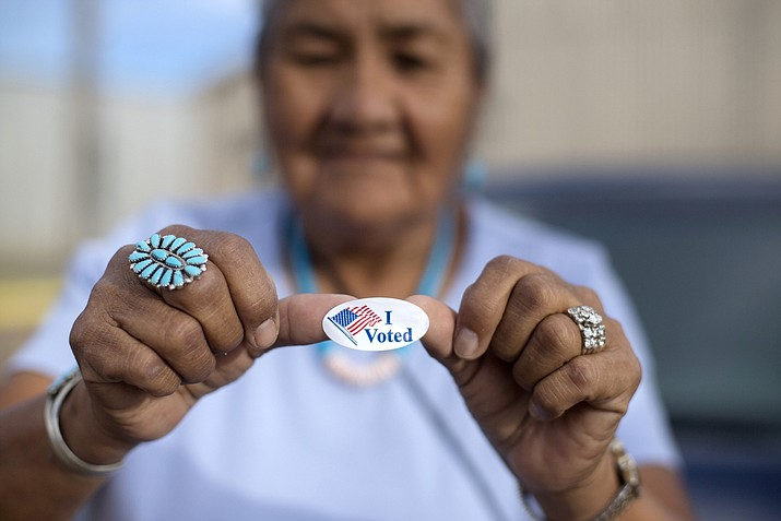 "In this Aug. 28, 2018 file photo, Mildred James of Sanders, Ariz., shows off her ""I Voted"" sticker as she waits for results of the Navajo Nation presidential primary election to be revealed in Window Rock, Ariz. (AP Photo/Cayla Nimmo, File)"