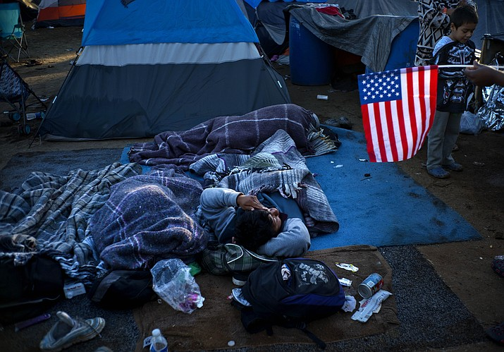 A migrant holding a U.S. flag, right, speaks with others waking up at the Benito Juarez Sports Center that's serving as a temporary shelter in Tijuana, Mexico, early Monday, Nov. 26, 2018. The mayor of Tijuana has declared a humanitarian crisis in his border city and says that he has asked the United Nations for aid to deal with thousands of Central American migrants who have arrived in the city. (Ramon Espinosa/AP)