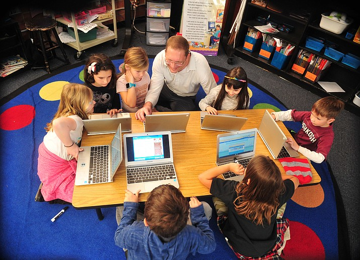 Prescott Unified School District Chief Financial Officer Brian Moore interacts with second-graders at Taylor Hicks Elementary School as they work on their Chromebooks during class Wednesday, Nov. 28, 2018. (Les Stukenberg/Courier)