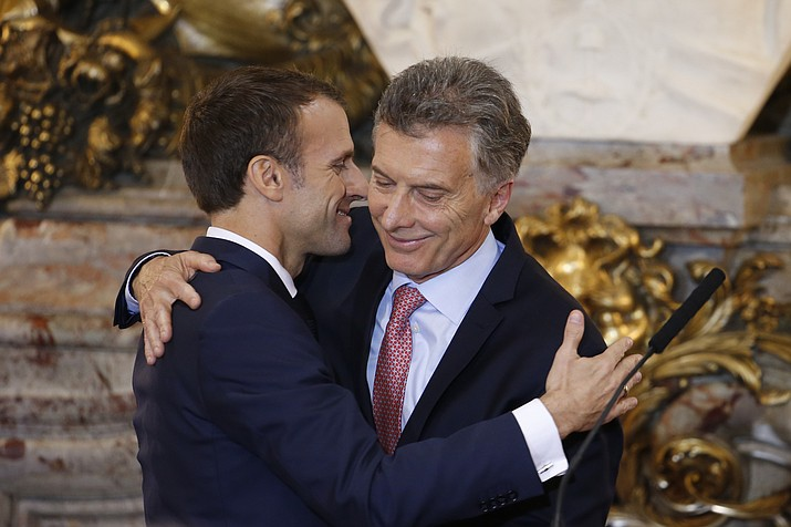 France's President Emmanuel Macron, left, and Argentina's President Mauricio Macri embrace after a joint press conference at the presidential palace in Buenos Aires, Argentina, Thursday, Nov. 29, 2018. Macron will attend the G20 starting Friday. (AP Photo/Natacha Pisarenko)