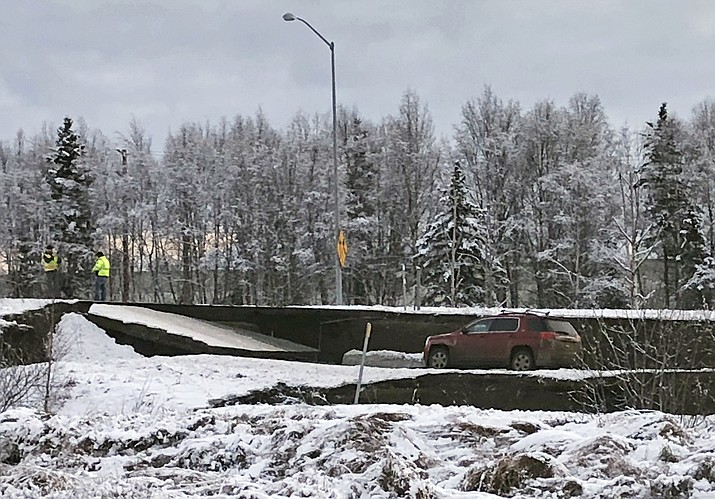 A car is trapped on a collapsed section of the offramp off of Minnesota Drive in Anchorage, Friday, Nov. 30, 2018. Back-to-back earthquakes measuring 7.0 and 5.8 rocked buildings and buckled roads Friday morning in Anchorage, prompting people to run from their offices or seek shelter under office desks, while a tsunami warning had some seeking higher ground. (AP Photo/Dan Joling)