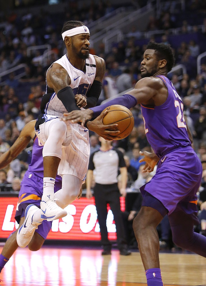 Orlando Magic guard Terrence Ross passes the ball around Phoenix Suns center Deandre Ayton (22) during the first half of an NBA basketball game Friday, Nov. 30, 2018, in Phoenix. (Rick Scuteri/AP)