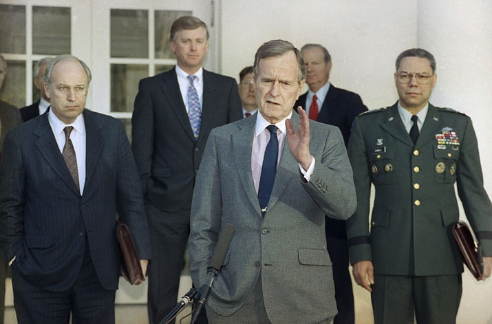 In this Feb. 11, 1991, file photo, President George H.W. Bush talks to reporters in the Rose Garden of the White House after meeting with top military advisors to discuss the Persian Gulf War. From left are, Defense Secretary Dick Cheney, Vice President Dan Quayle, White House Chief of Staff John Sununu, the president, Secretary of State James A. Baker III, and Joint Chiefs Chairman Gen. Colin Powell. Bush died at the age of 94 on Friday, Nov. 30, 2018, about eight months after the death of his wife, Barbara Bush. (AP Photo/Ron Edmonds, File)