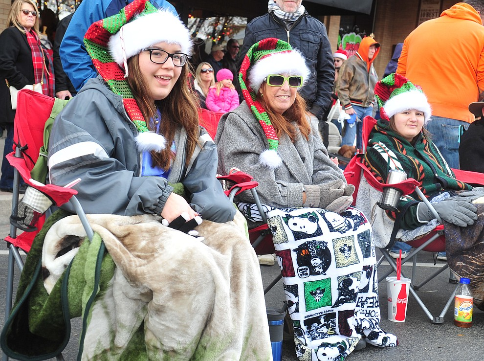 Espy Careaga, Eowyn Scola and Celeste Careaga watch as ninety floats, marching bands and special groups participate in the 38th annual Prescott Chamber Christmas Parade in downtown Prescott Satuday, Dec. 1, 2018. (Les Stukenberg/Courier).