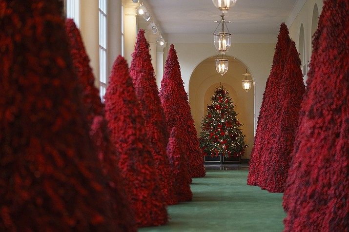 """Topiary trees line the East colonnade during the 2018 Christmas Press Preview at the White House in Washington, Monday, Nov. 26, 2018. Christmas has arrived at the White House. First lady Melania Trump unveiled the 2018 White House holiday decor on Monday. She designed the decor, which features a theme of """"American Treasures."""" (Carolyn Kaster/AP)"""