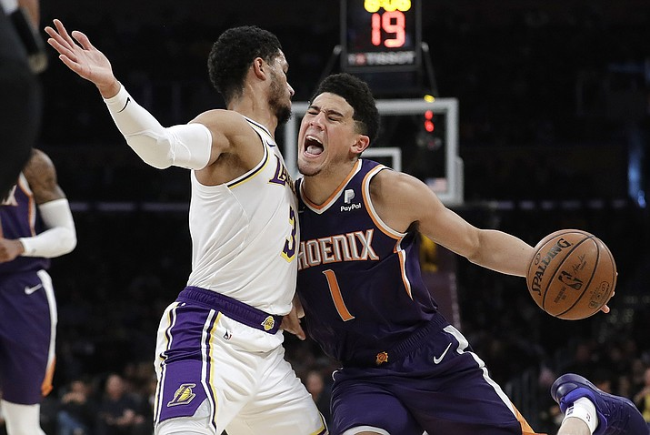 Phoenix Suns' Devin Booker (1) is defended by Los Angeles Lakers' Josh Hart (3) during the first half of an NBA basketball game Sunday, Dec. 2, 2018, in Los Angeles. (Marcio Jose Sanchez/AP)