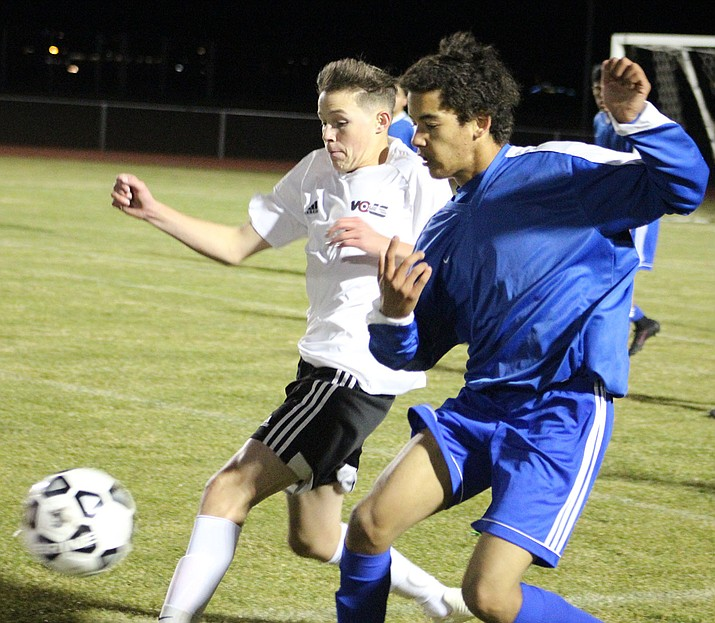 Lee Williams' Gabe Otero, left, tallied the assist on TJ Cabonovich's game-winning goal Monday night in a 3-2 double overtime victory against Kingman High. (Photo by Beau Bearden/Daily Miner)