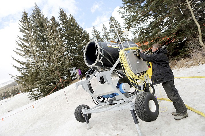 In this file photo taken on March 3, 2014, snowmaking supervisor Carl McKenna explains the features of a snowmaking machine at the Arizona Snowbowl near Flagstaff, Ariz. The Arizona Supreme Court is scheduled to rule on the Hopi Tribe's challenge to snowmaking at a northern Arizona ski resort. The decision is expected mid-morning Thursday, Nov. 29, 2018. The high court has been considering whether a lower court created a new category of special harm for public nuisance claims. (Jake Bacon/Arizona Daily Sun via AP, File)