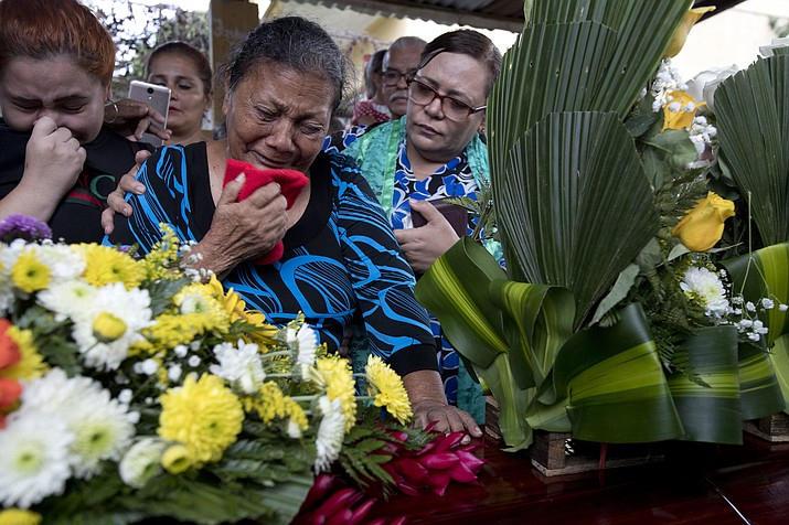 In this Oct. 31, 2018 photo, Haydee Posadas cries during the burial service for her son Wilmer Gerardo Nunez, at a cemetery in San Pedro Sula, Honduras. Two weeks after Nunez left Honduras for the U.S, when Posadas turned on the television news, fear suddenly gripped her. Authorities had found 72 corpses of migrants on a ranch in San Fernando, across the border from Texas. (AP Photo/Moises Castillo)