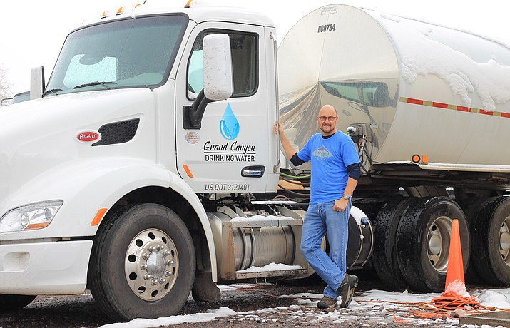 Brian Predmore stands next to one of the Grand Canyon Drinking Water trucks on State Route 64. Predmore is credited with helping put out a shed fire while delivering water to a Garland Prairie residence. (Wendy Howell/WGCN)