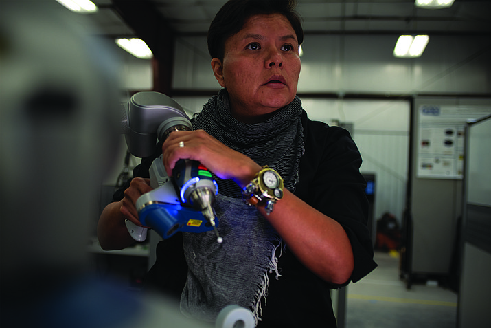 Marcie Vandever of Thoreau, New Mexico operates the Faro Tracker Arm while conducting measurements of a 3D printed object. Metrology will be an important focus of Navajo Technical University's new Center for Advanced Manufacturing.