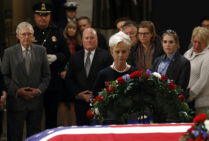 Cindy McCain, center, widow of the late U.S> Sen. John McCain, R-Ariz., views the flag-draped casket of former President George H.W. Bush as he lies in state in the Capitol Rotunda in Washington, Tuesday, Dec. 4, 2018. At back left is Senate Majority Leader Mitch McConnell, R-Ky. (Patrick Semansky/AP)