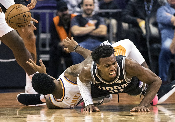 Sacramento Kings' Buddy Hield (24) falls hard as he battles for a ball with Phoenix Suns' Troy Daniels (30) during the first half of an NBA basketball game, Tuesday, Dec. 4, 2018, in Phoenix. (Darryl Webb/AP)
