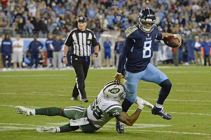 Tennessee Titans quarterback Marcus Mariota (8) gets out of the grasp of New York Jets inside linebacker Darron Lee (58) in the second half of an NFL football game Sunday, Dec. 2, 2018, in Nashville, Tenn. (Mark Zaleski/AP)