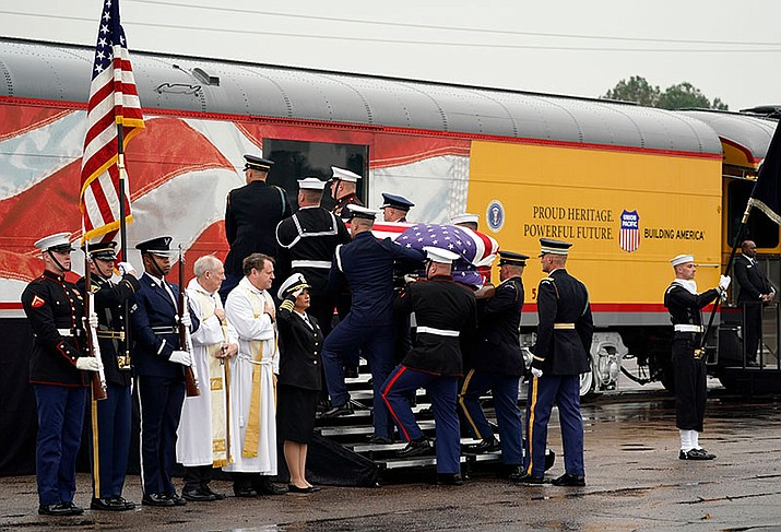 The flag-draped casket of former President George H.W. Bush is carried by a joint services military honor guard Thursday, in Spring, Texas, as it is placed on a Union Pacific train. (AP Photo/David J. Phillip, Pool)