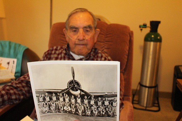Bob Campbell, 95, holds a photo of his 1942 graduating class from the Naval Aviator program in his room at White Cliffs Senior Center. He flew Grumman Avenger torpedo bomber planes in World War II. (Photo by Hubble Ray Smith/Daily Miner)
