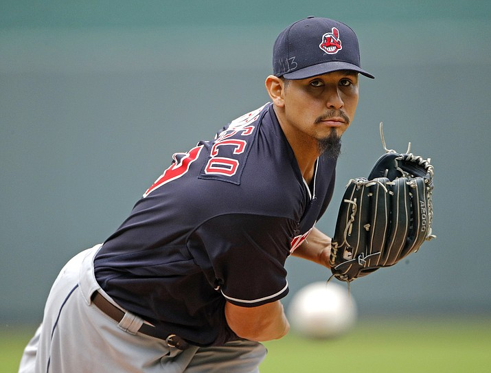 In this Sept. 30, 2018, file photo, Cleveland Indians starting pitcher Carlos Carrasco throws during the first inning of a baseball game against the Kansas City Royals in Kansas City, Mo. The Indians have signed Carrasco to a new, four-year contract through the 2022 season. Carrasco's deal includes a club option for 2023. Financial terms of the contract were not immediately available. (Charlie Riedel/AP, File)