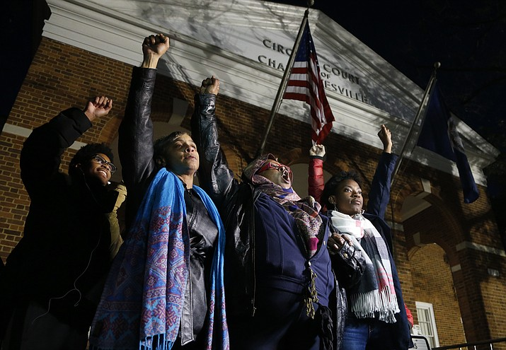 """Local activists raise their fists outside Charlottesville General District Court after a guilty verdict was reached in the trial of James Alex Fields Jr., in Charlottesville, Va., Friday, Dec. 7, 2018. Fields was convicted of first degree murder in the death of Heather Heyer as well as nine other counts during a """"Unite the Right"""" rally in Charlottesville. (Steve Helber/AP)"""