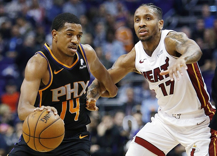 Phoenix guard De'Anthony Melton drives on Miami forward Rodney McGruder during the second half Friday, Dec. 7, 2018, in Phoenix. (Rick Scuteri/AP)